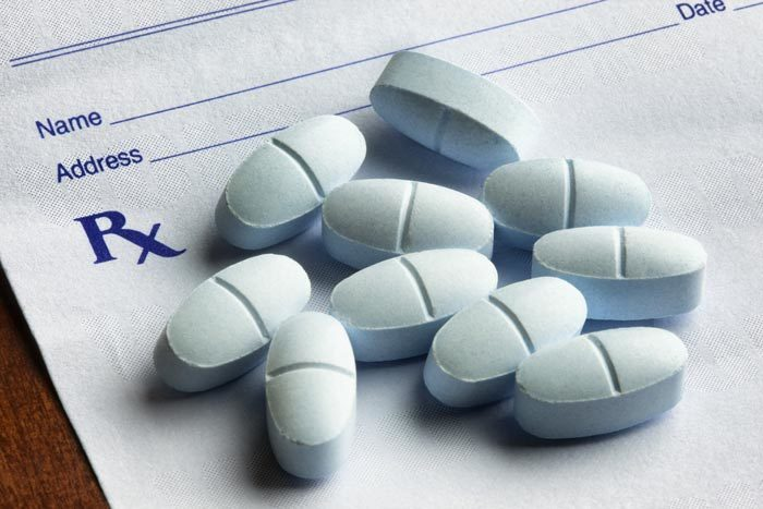 Opioid pills on top of a white prescription pad