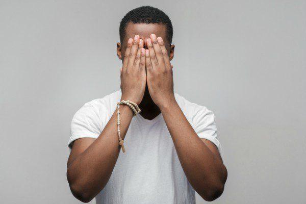 Black man hiding his face