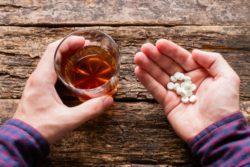 Man holding liquor glass and pills