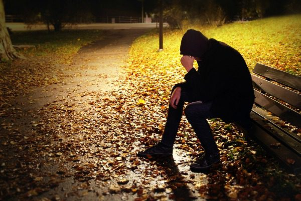Man in hoodie on park bench at night