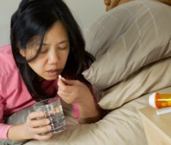 Woman taking sedative in bed
