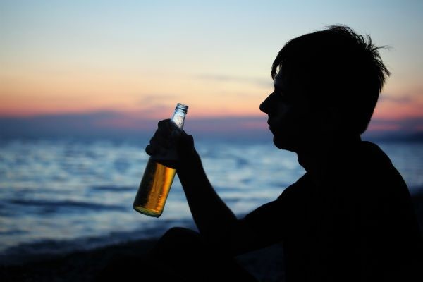 Young drinker on the beach
